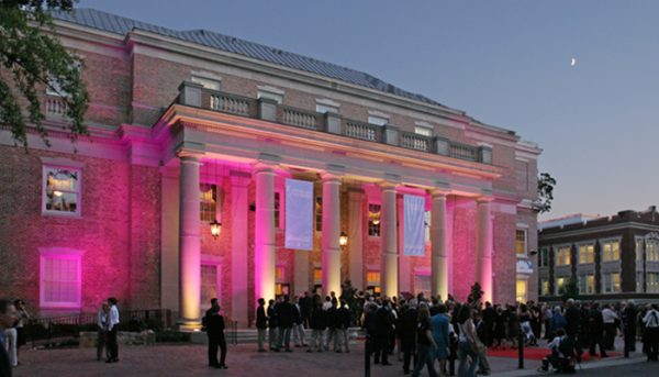A an exterior view of a performing arts venue, lit up with pink lights in between its large columns.