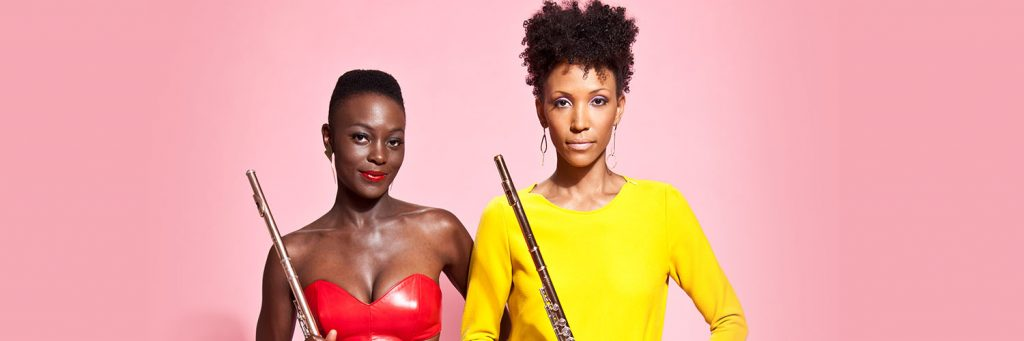 Two women wearing brightly colored clothes and holding flutes