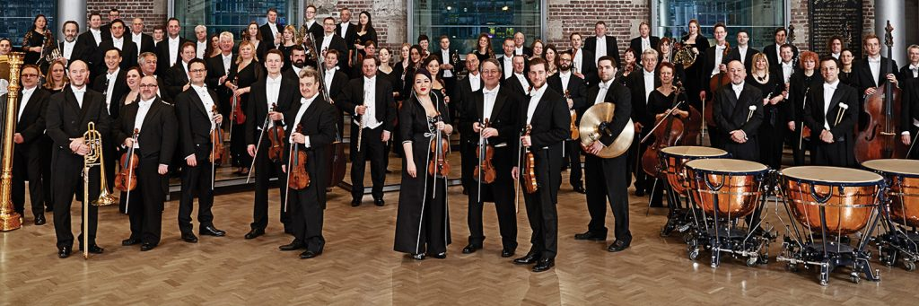 Members of the London Symphony Orchestra dressed in black tie apparel stand with their instruments.