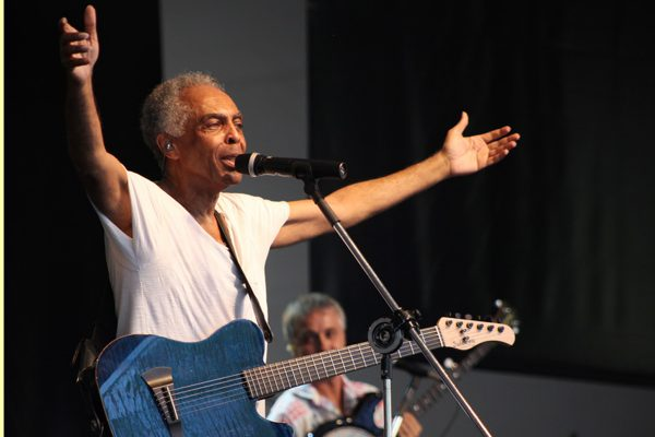 A woman wearing a white t-shirt sings with her arms outstretched.