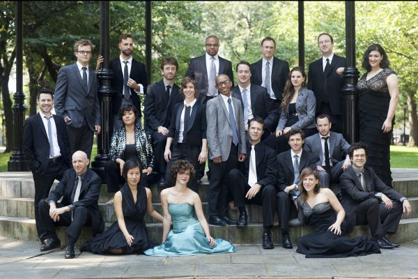 A group of people in suits and formal dresses sit for a formal group picture in a park.