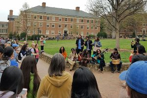 A group of people gather around students who are performing in UNC's quad.