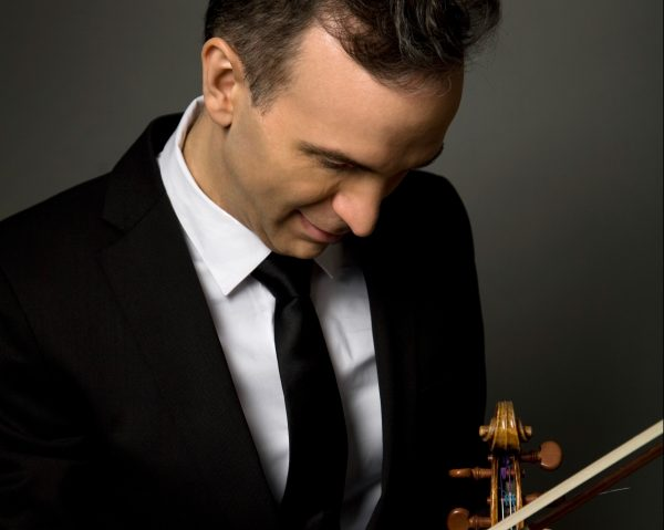 A man in a suit looks down at a violin.