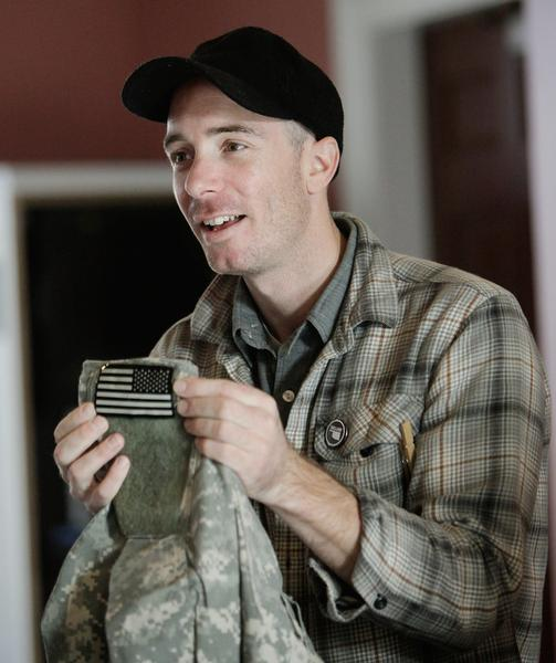 A man in a plaid shirt and black hat holds military fatigues with an American flag patch featured prominently.