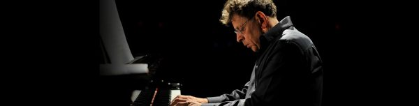 Philip Glass, composer, sits at a piano.