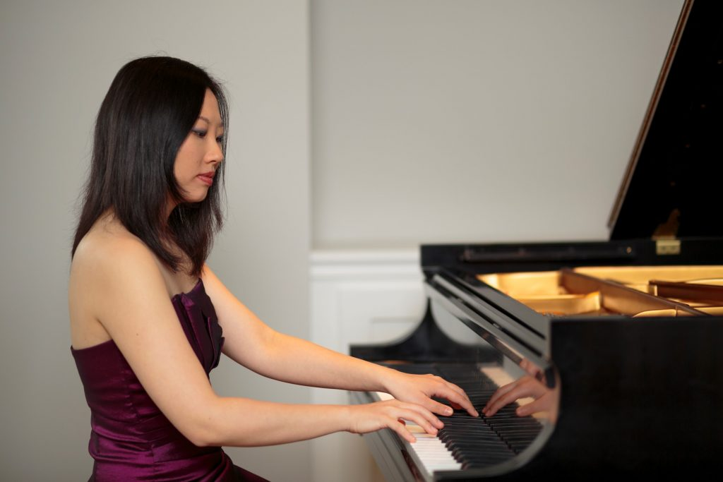 A woman in a dress plays the grand piano.