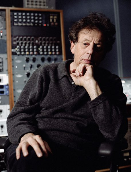Philip Glass sits at a sound board.