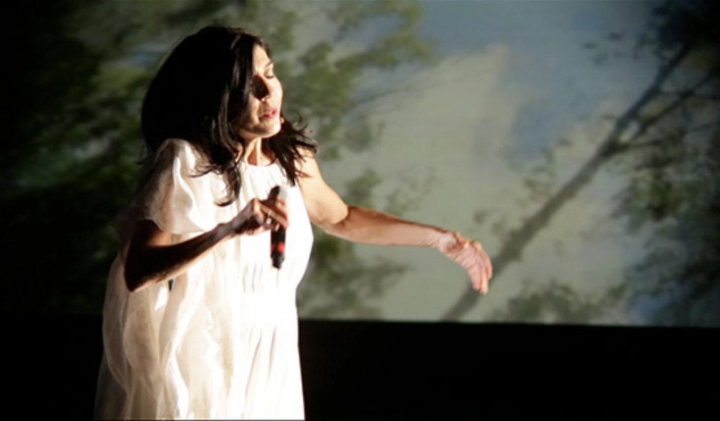 A woman wearing a white dress dances on stage while holding a microphone.