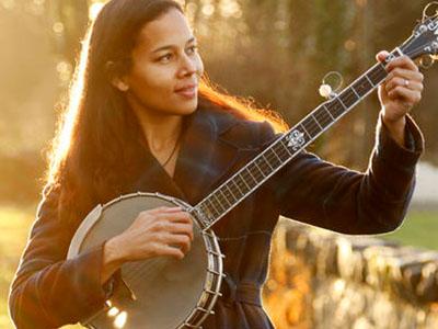 A woman tunes a banjo in a sunlit field.