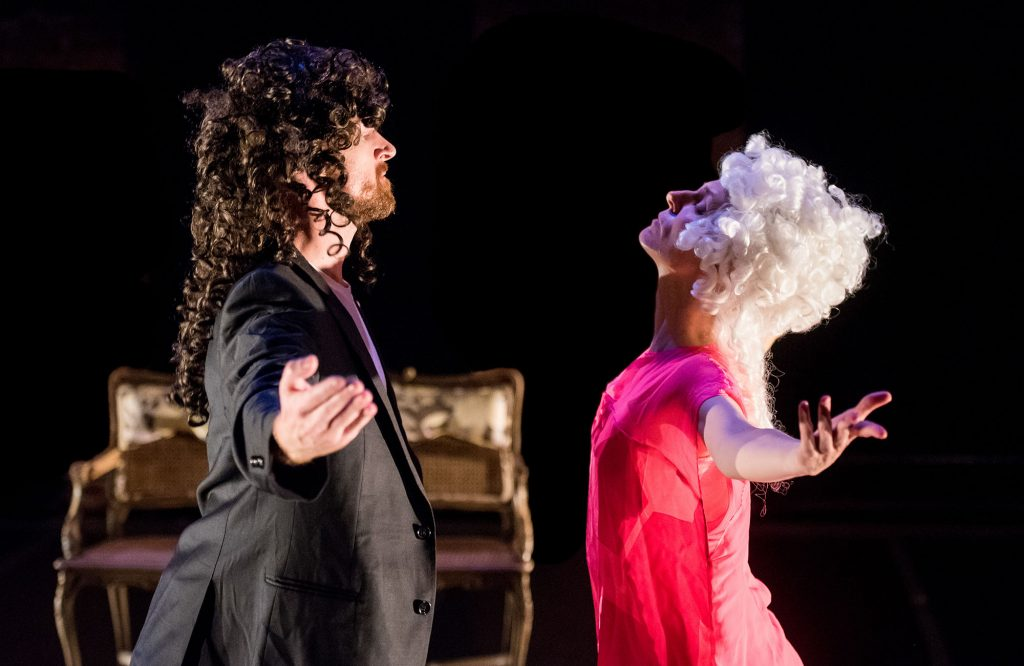 A man in a suit and a woman in pink clothes and fluffy, white wig bow to each other on stage.