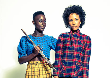 Two women in plaid clothing holding flutes.