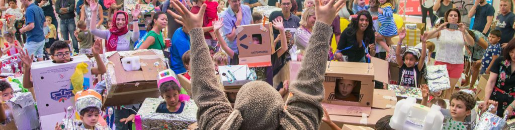 A crowd of children celebrate in their homemade robot costumes