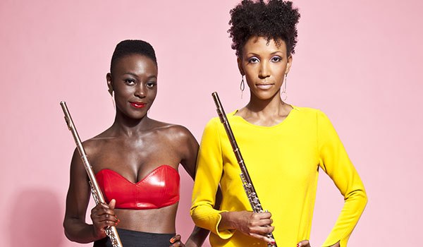 Two women in bright clothing pose with their flutes.