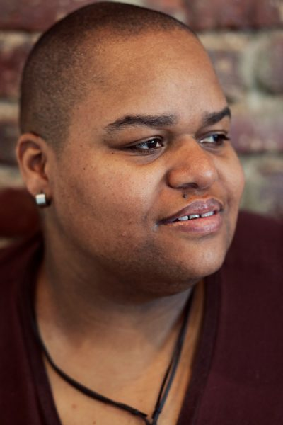 Artist-in-residence Toshi Reagon poses for a headshot in front of a brick wall