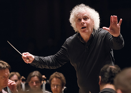 Conductor Sir Simon Rattle conducts the London Symphony Orchestra with emotion.
