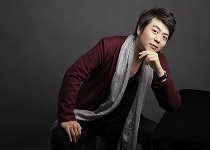 Pianist Lang Lang sits at a piano bench wearing a red blazer and grey scarf.