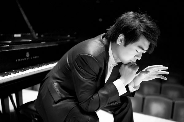 Pianist Lang Lang sits at his piano bench in deep concentration.