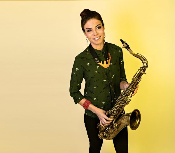 Saxophonist Melissa Aldana stands in front of a yellow background with her saxophone in her hands.