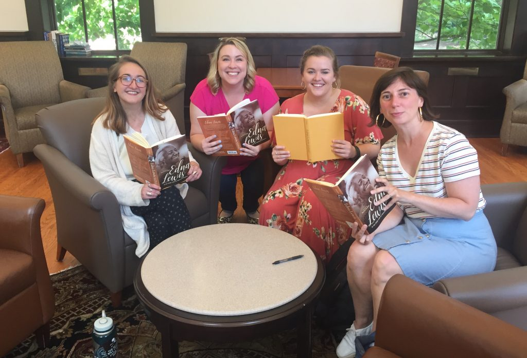 Four women smile as they hold books they've been reading and discussing together.