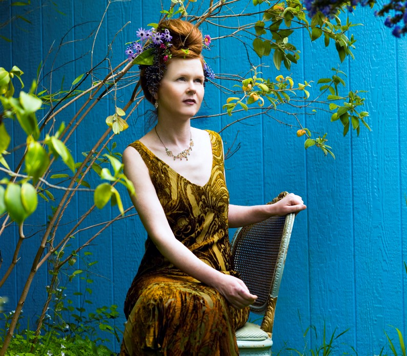 Composer Sarah Cahill wearing a yellow, vintage dress sits amongst foliage, a flower crown in her hair.