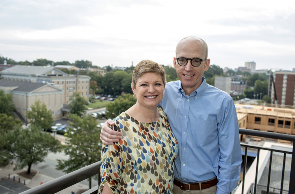 A man and a woman stand side-by-side, smiling, on a balcony overlooking downtown Chapel Hill.