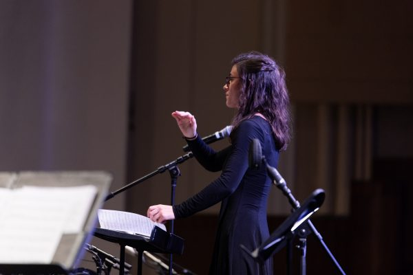 Composer Eliana Fishbeyn conducts an ensemble with her back to the audience.