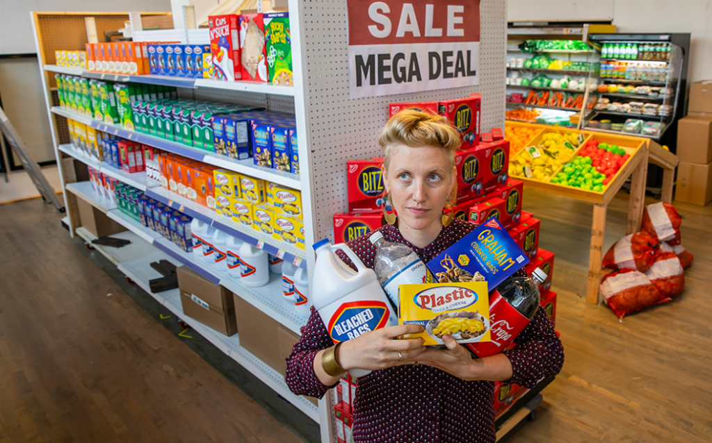 Woman with blonde hair stands with arms full of grocery items in what looks like a convenience store.