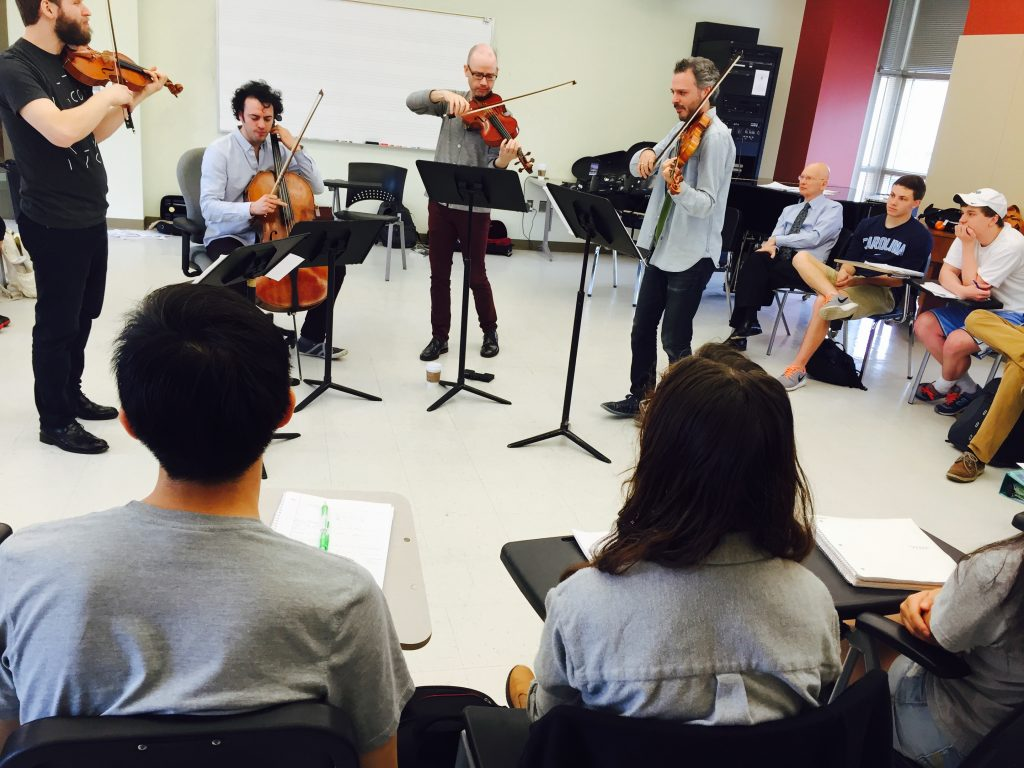 String quartet standing at music stands in a classroom, with seated students watching them play