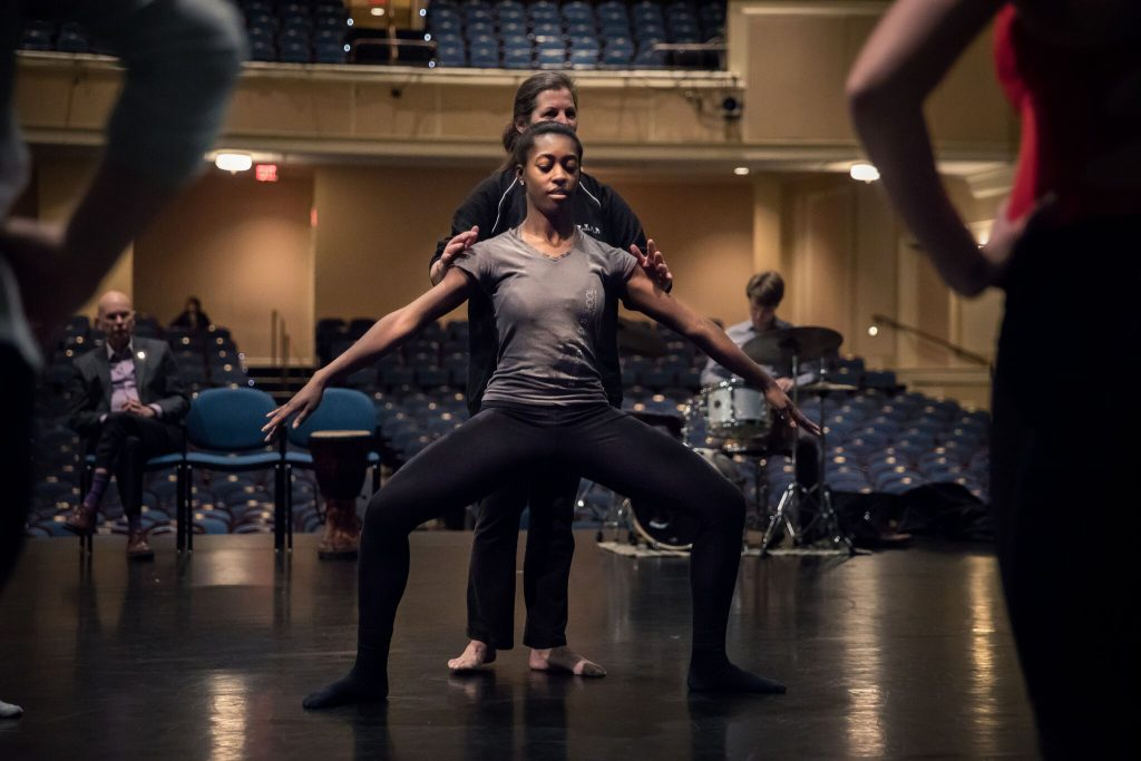 Student dancer in wide plié, with person behind them helping adjust their form, onstage at UNC's Memorial Hall, facing toward the house.