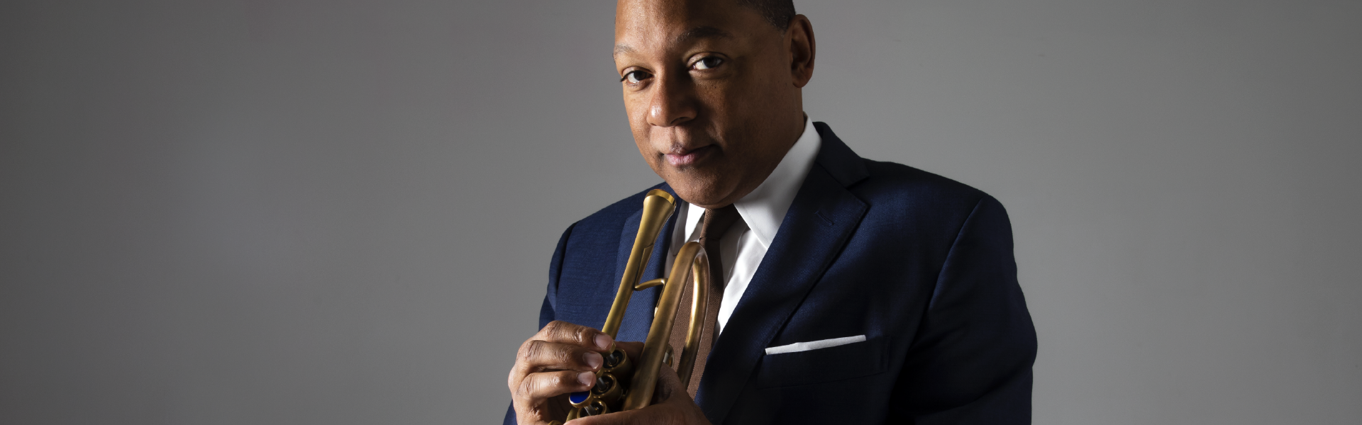 Wynton Marsalis stands with his trumpet.