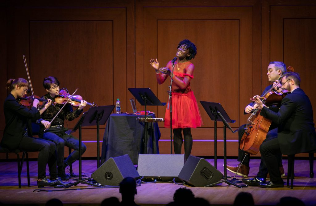A Black woman in a red dress sings on a stage with a string quartet