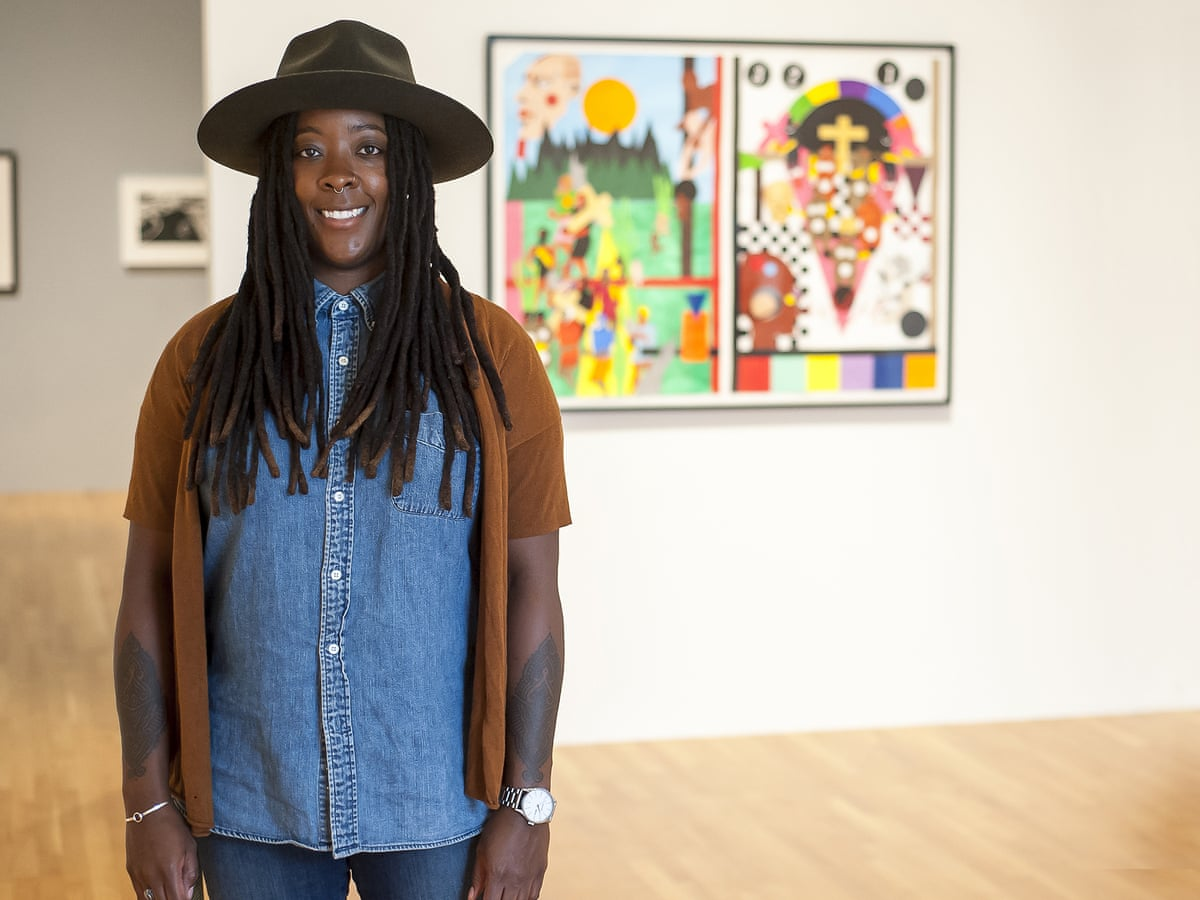 Artist Nina Chanel Abney stands in front of her artwork at a museum.