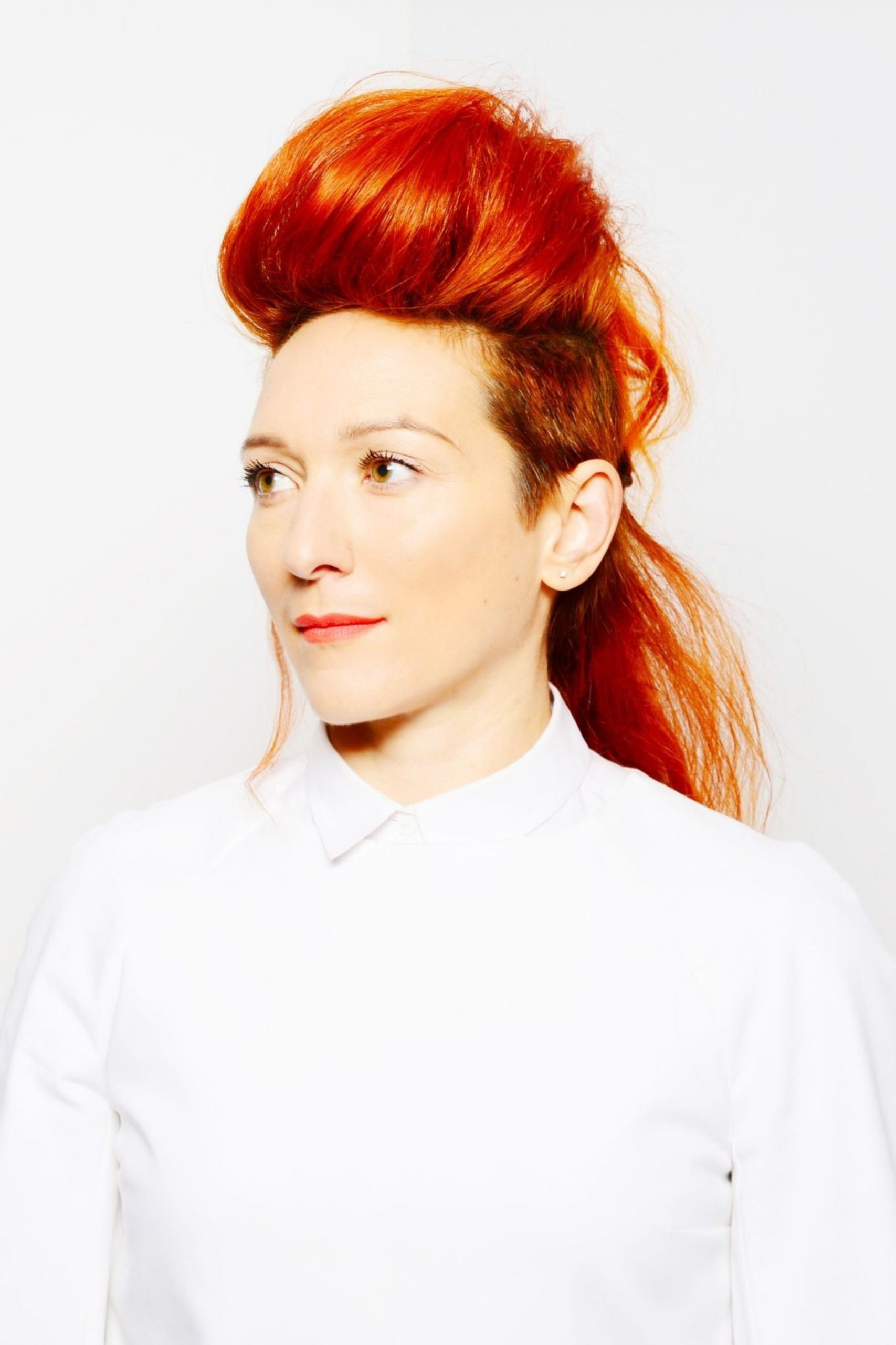 Shara Nova wears a white collared shirt, her bright red hair in a bun.