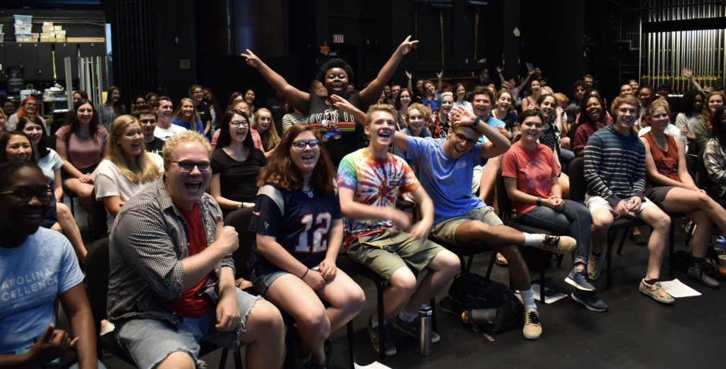 Students smile and cheer at the beginning of student staff orientation on Memorial Hall's stage.