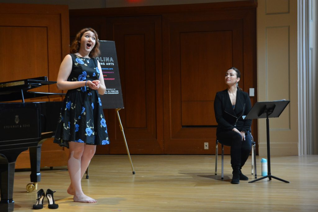 A student singer performs for opera singer Isabel Leonard, who listens while smiling.
