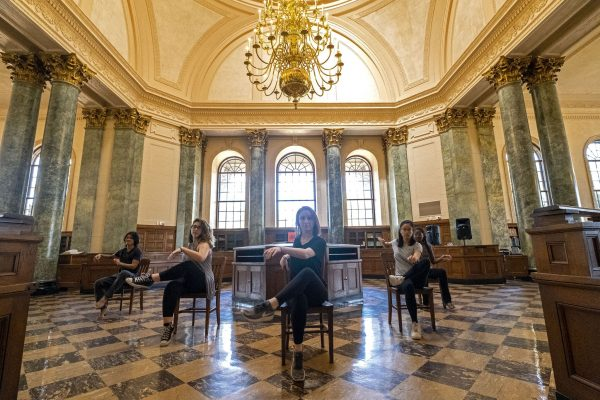 Dancers seated in v-formation inside Fearrington Reading Room in UNC's Wilson Library