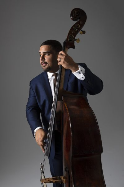 Carlos Henriquez of Jazz at Lincoln Center plays his bass in a blue suit.