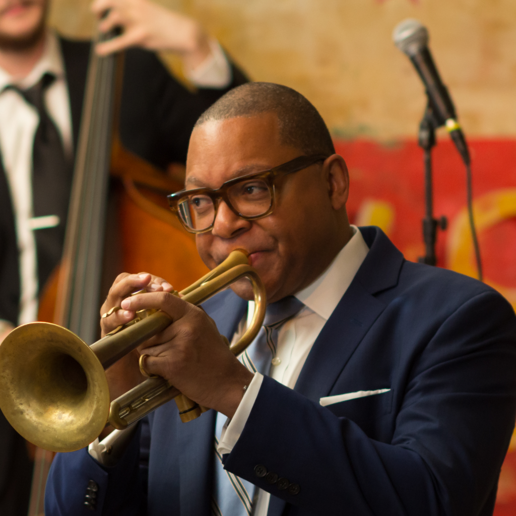 Musician Wynton Marsalis plays the trumpet in front of a colorful mural.