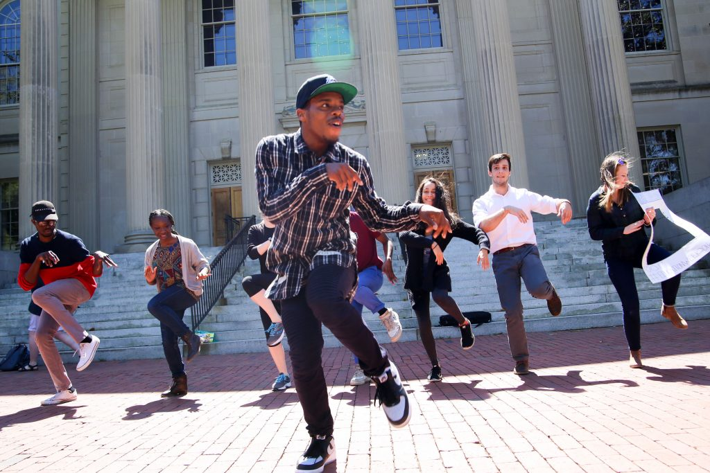 Young man (dancer Lil Buck) dances with seven students lined up behind him outside Wilson Library at the University of North Carolina at Chapel Hill as part of the Carolina Performing Arts' pop-up event