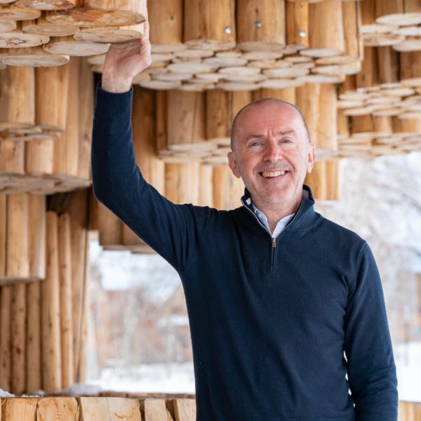 Pianist Pedja Muzijevic stands underneath a geometric wooden sculpture.