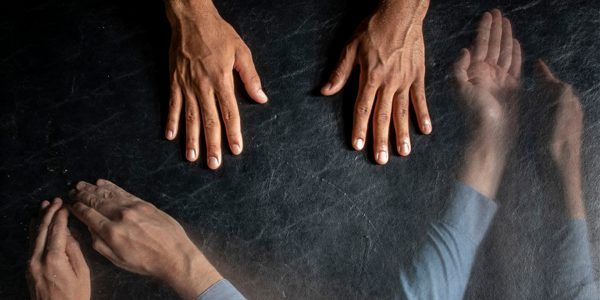 Three sets of hands move across a dark backround