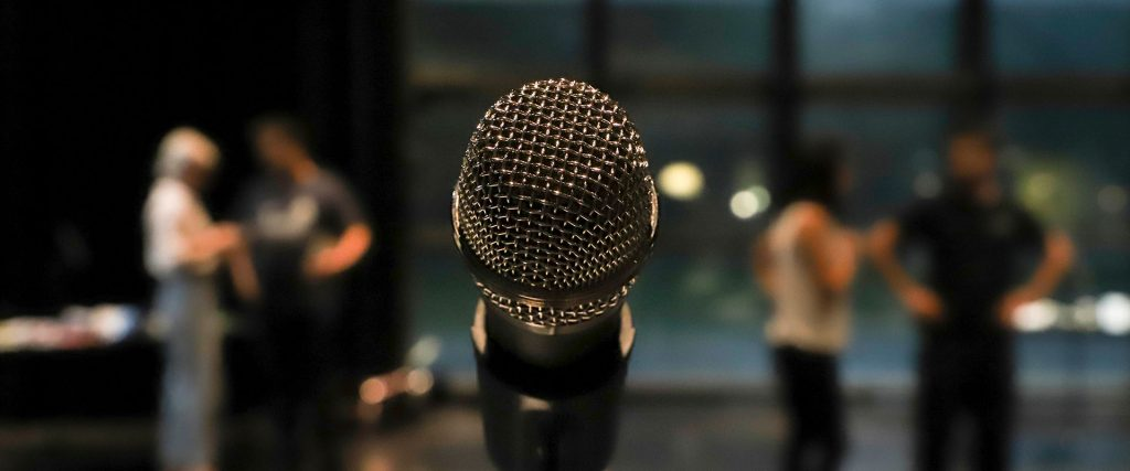 close up image of a microphone on a stand with blurred people standing in the background