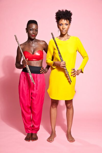 Nathalie Joachim and Allison Loggins-Hull of Flutronix stand side by side with their flutes in bright attire.