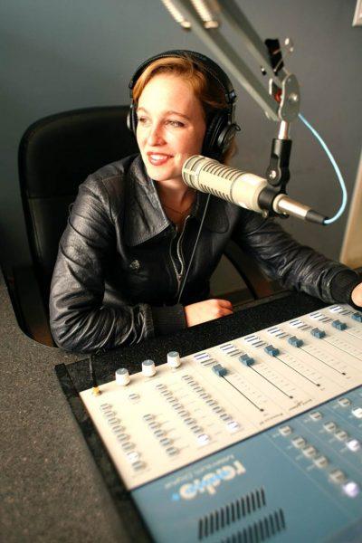 Artist Tift Merritt sits at a sound board in a recording studio.