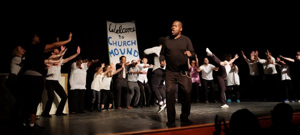"Black man dressed in black on foreground of stage, with several people in background holding up a hand-painted sign that says ""Welcome to Church Mound"""