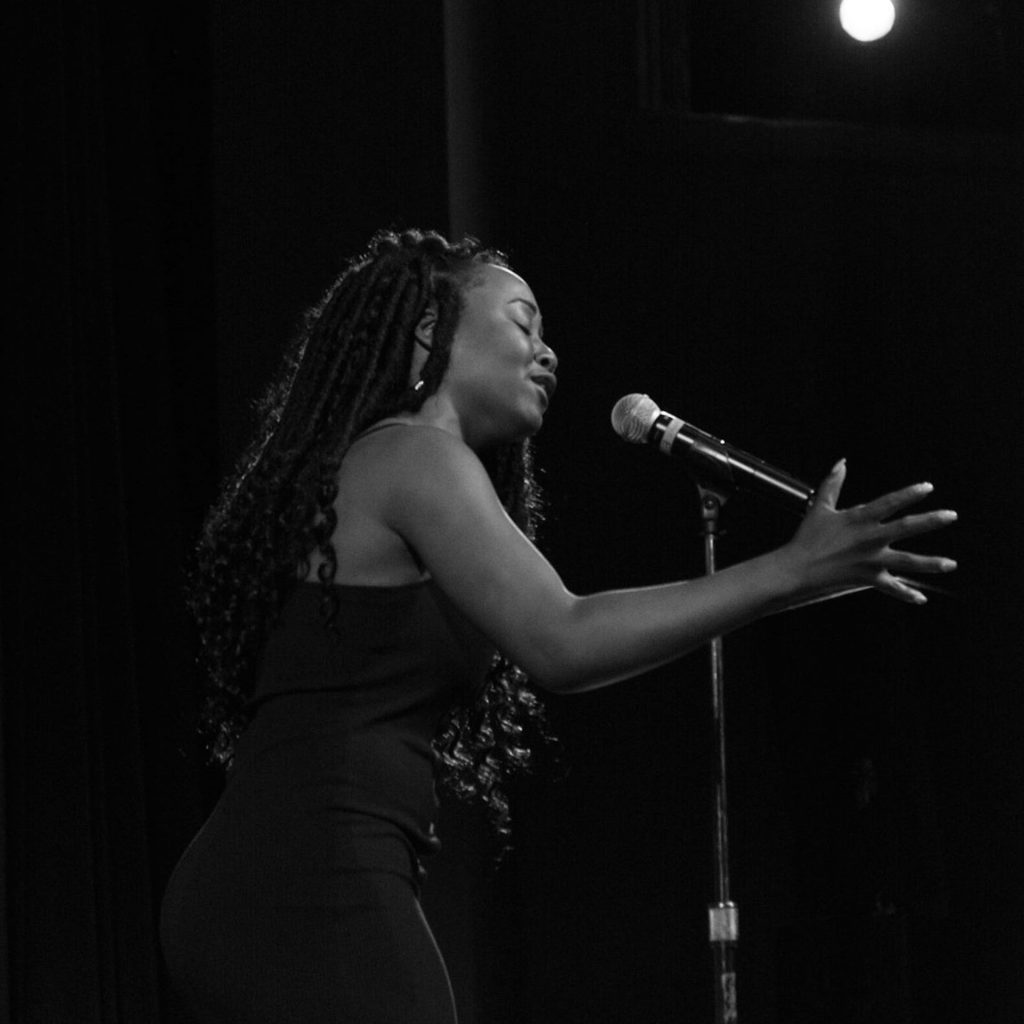 black and white image of a young Black woman with braids and a dark dress singing into a microphone