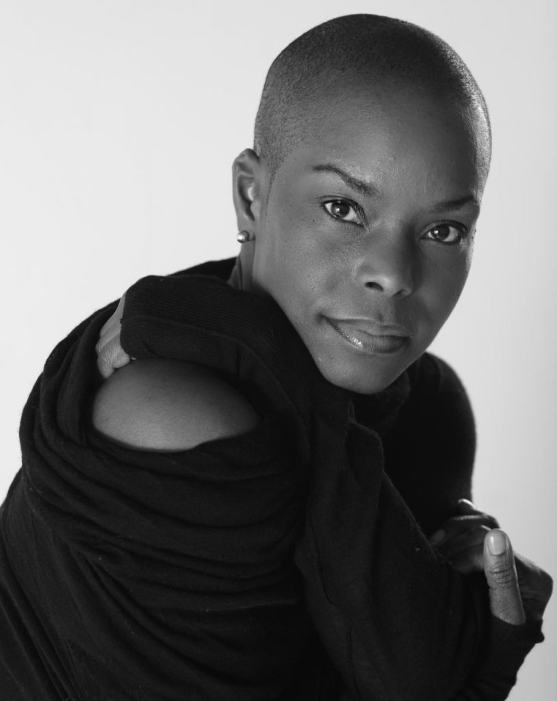 Dancer Hope Boykin looks at the camera wearing a off-the-shoulder black sweater.