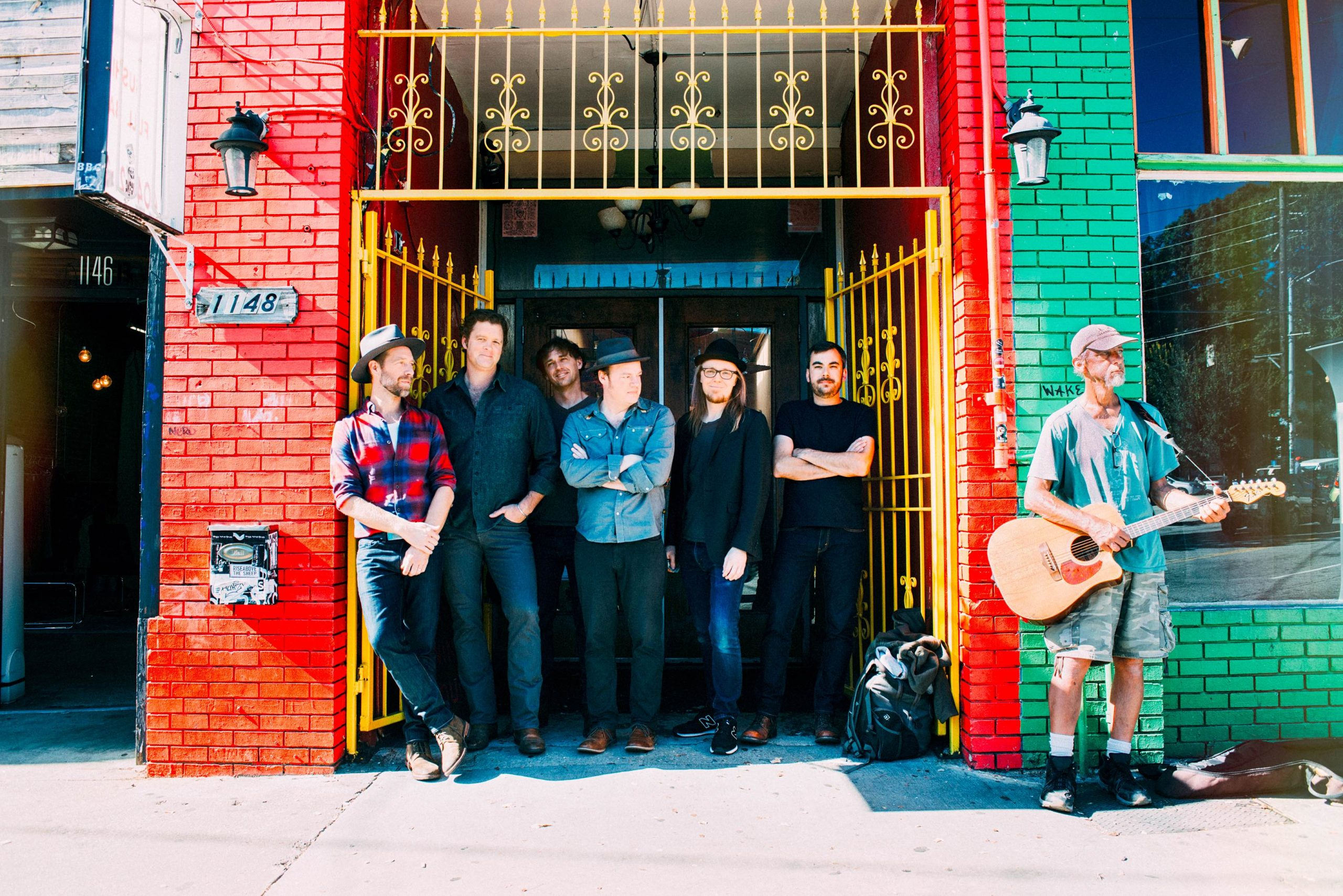 The band Steep Canyon Rangers stands together in front of a brightly colored brick building.