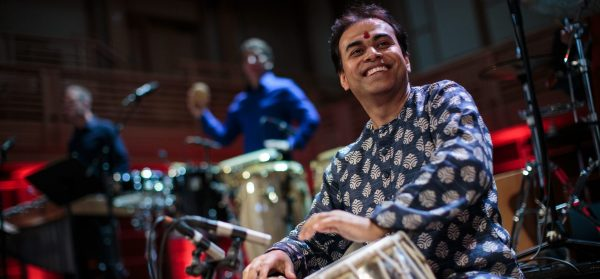 Sandeep Das, an Indian man wearing a blue and white patterned shirt, sits while playing the table, a drum