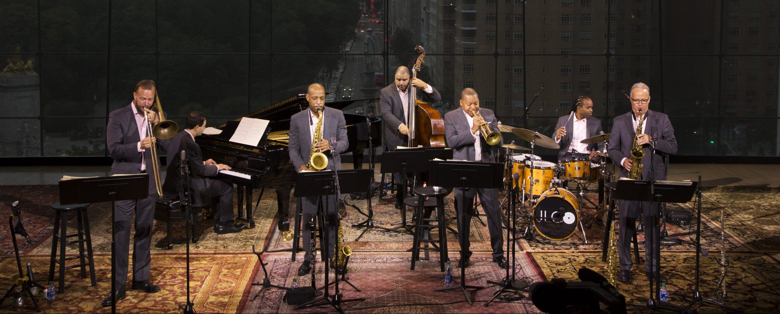 Seven men from the Jazz at Lincoln Center Orchestra stand on a stage and play their instruments